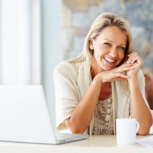 white woman with blonde hair sitting at a desk with a cup of coffee and a laptop as she smiles