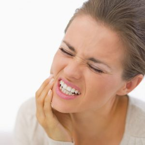 close up of a woman grimacing and holding her jaw in pain