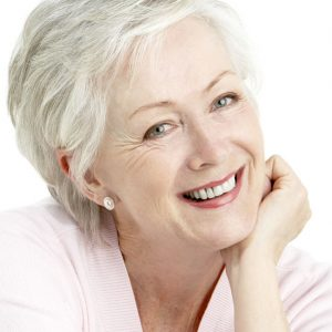 an elderly white woman with short hair wearing a pink sweater and smiling as she rests her head on her hand