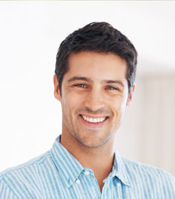 picture of a white man with dark hair in a blue shirt smiling