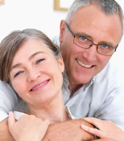 close up of an older woman smiling as her husband wraps his arms around her from behind as he smiles