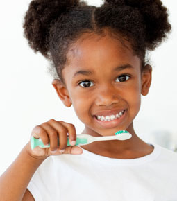 picture of a young black girl holding a toothbrush and smiling