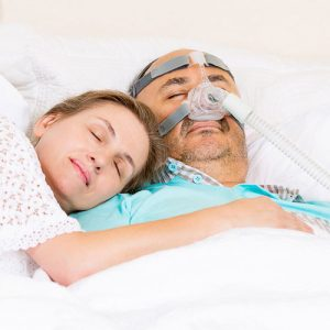a woman lays peacefully on the chest of her sleeping husband as he wears a CPAP mask to sleep