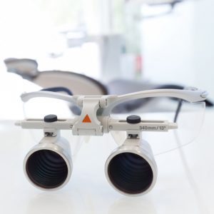 picture of a dentist's glasses with magnification sitting on a table in front of a dental chair