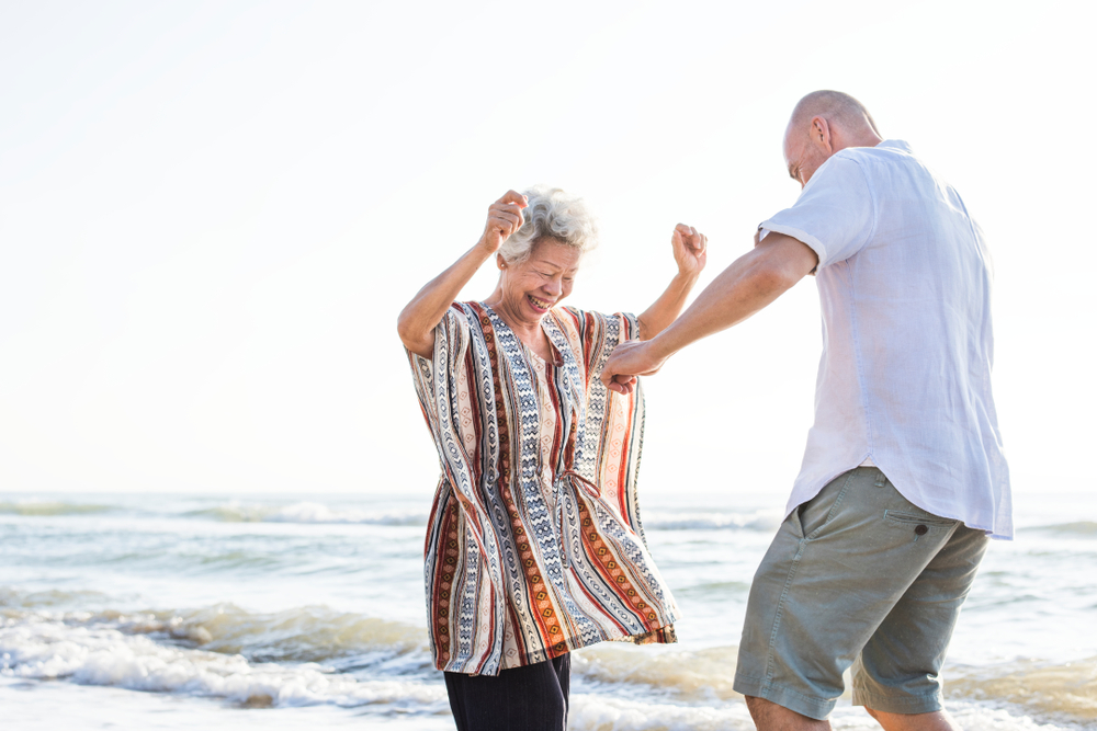A woman dances with her son enjoying the benefits of her dental crowns.
