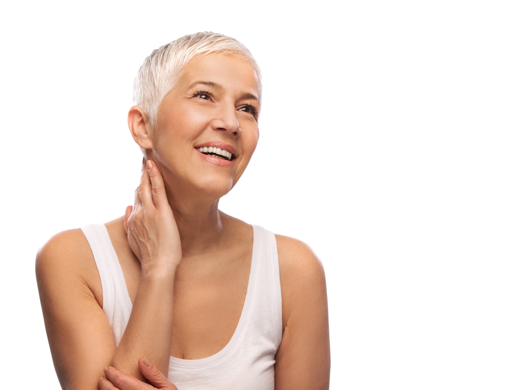 A woman with short, white hair smiles. Her skin is moisturized and youthful thanks to cosmetic facial treatments.